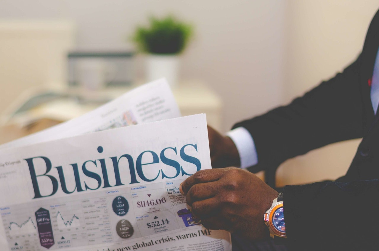 person-holding-white-and-blue-business-paper-936137